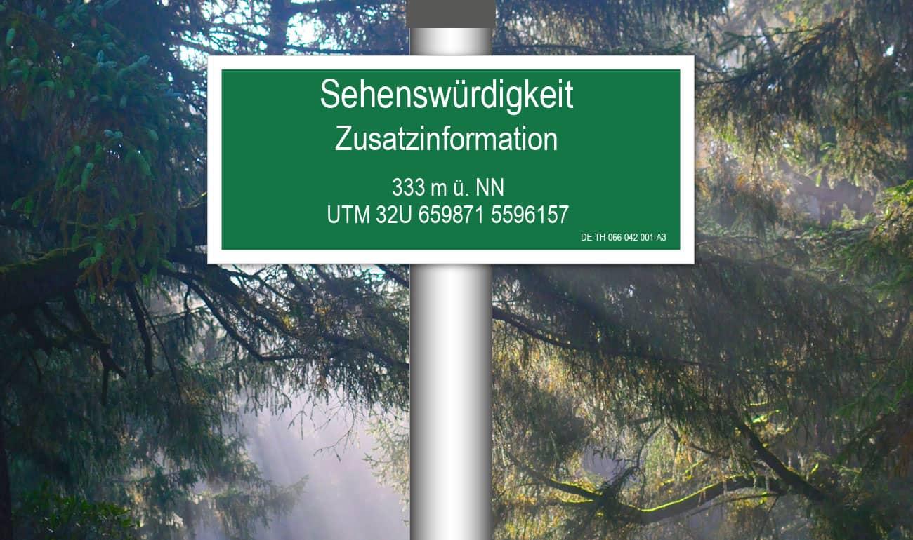 grünes, rechteckiges Schild mit weißer Schrift im Hintergrund Wald